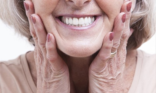 older woman holding her face as she smiles with dentures