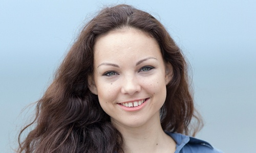 A young woman wearing a denim button-down blouse and smiling, showing off the spaces in-between teeth in Vienna