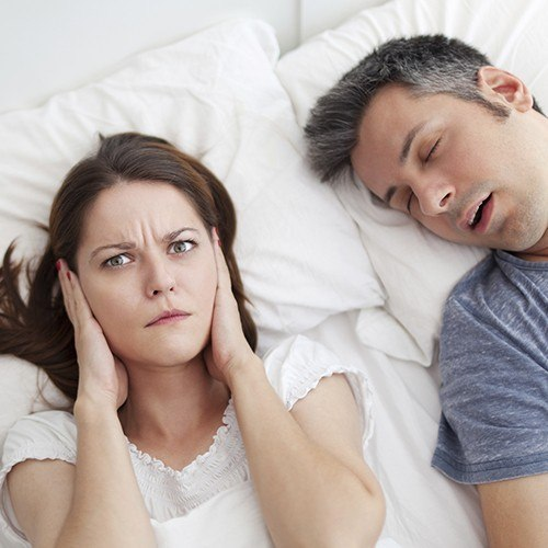 Woman covering ears next to snoring man in bed