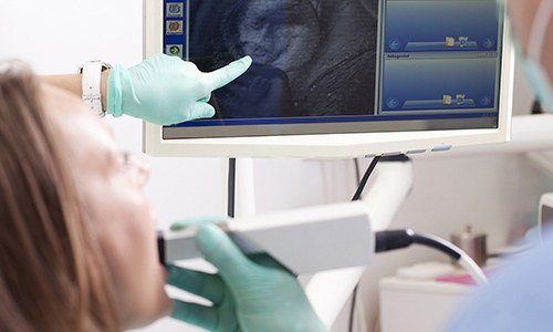 Patient and dentist looking at intraoral photos